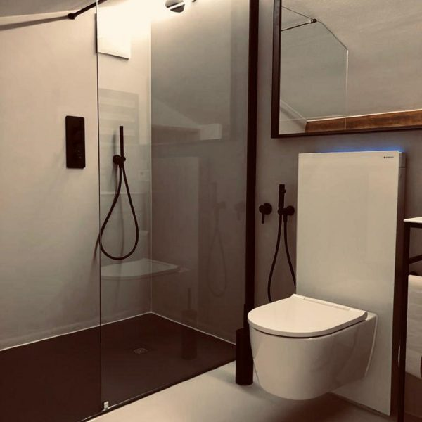 Barrierefreie Badsanierung mit fugenloser Oberfläche mit Glasspülkasten, spülrandlosem WC, Waschtisch-Anlage, LED-Lichtspiegel und Badetuchtrockner 001