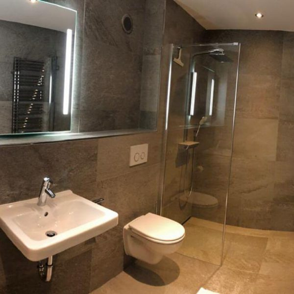 Barrierefreie Badsanierung von einem Gäste-Bad mit Komfort-Duschanlage mit Hansgrohe Rainshower, Handwaschbecken-Anlage mit Lichtspiegel und spülrandlosem WC 001